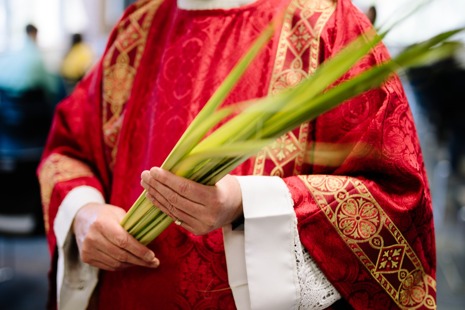 priest holding palm leaves